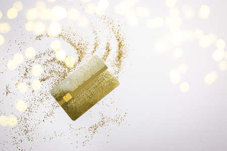 Golden dust or powder with gold credit card on white background, top view , copy space