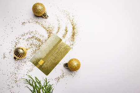 Online christmas shopping concept with christmas balls, golden dust and mockup of golden credit card on white background. Top view, flat lay