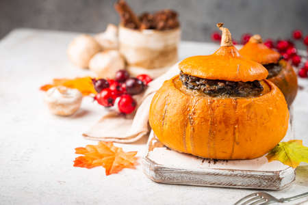Tasty autumn stuffed pumpkin with fresh mushrooms, spinach and vegetables ready on rustic white table