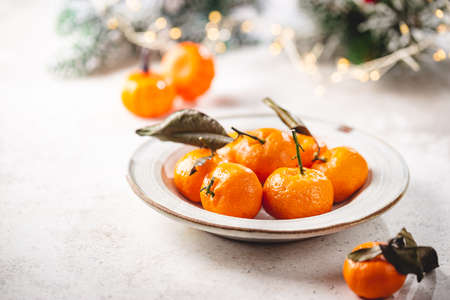 Fresh mandarin fruit or tangerines with leaves in a bowl on white background with winter decorations