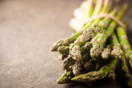 Bunch of fresh green asparagus spears on a rustic background