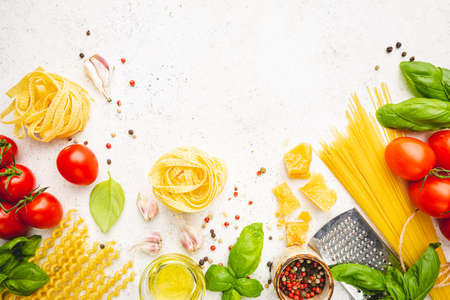 Pasta background. Several types of dry pasta with vegetables and herbs on white background. Free space for text. Top view