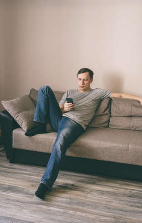 Serious man having rest using smartphone sitting on sofa at home Stockfoto