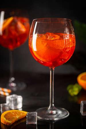 cocktail in glass with fresh orange on dark background