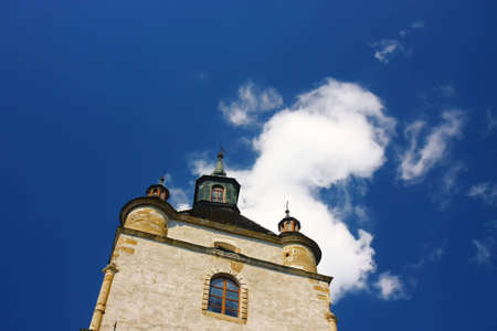 Old church tower in front of a cloud and a blue sky Standard-Bild