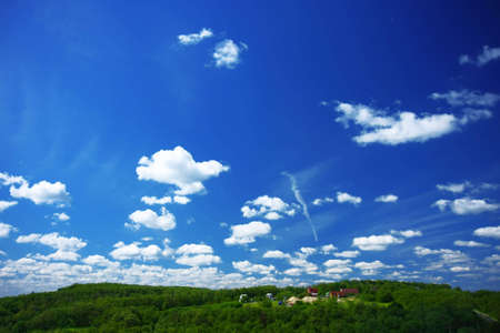 Image of a blue sky with the clouds on a sunny day and some rural houses in the green forest.