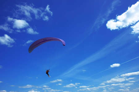 Paragliding on a sunny day with various clouds in the blue sky. Standard-Bild