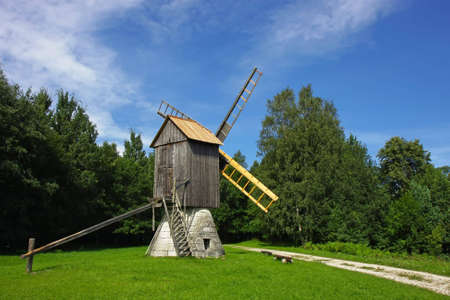 Scenic old wooden windmill in a countryside, surrounded by a green forest.