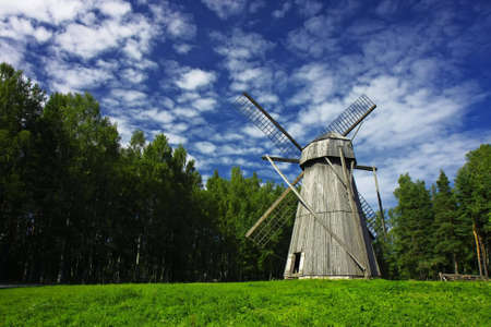 Old rural windmill on a meadow, surrounded by forest. High-contrast cloudscape.
