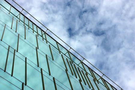 property management: Part of an office building facade reflecting the sky and clouds Stock Photo