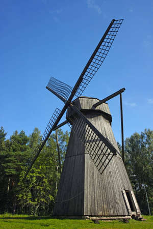 Old windmill made of wood with large blades in a scenic surrounding.