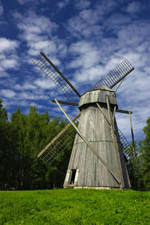 A vertical image of a large old windmill made of wood, typical for Northern Europe.  Standard-Bild