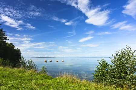 Idyllic seashore landscape with green grass, blue sky and vivid clouds