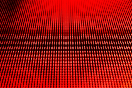 Red dot lights arranged on a video screen matrix. Shallow depth of field for a blurred effect.