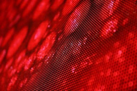 Angled view of an LED screen showing stylish red image. Shallow depth of field for a blurred effect.