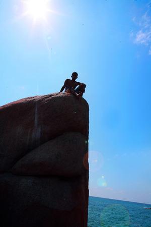 rockclimb: boy lokking sea on a rock