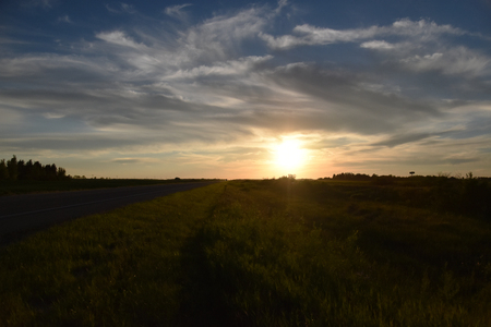 Sunset alongside a highway with big prairie skies Stock Photo