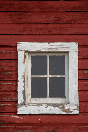 Square window with a white frame on an old red barn.