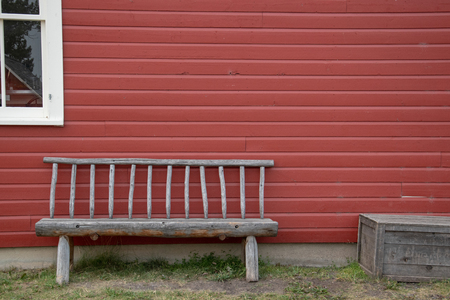 Timber bench and box against a red sided house with a white framed window pane