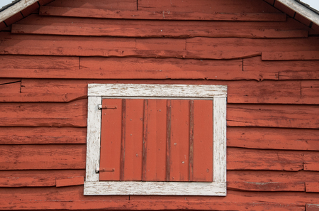 White framed hay loft door on an old red barn.