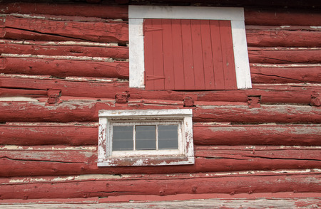 White framed hay loft door and windows on an old red barn. Stock Photo