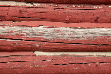 siding of an old red log barn with peeling paint.
