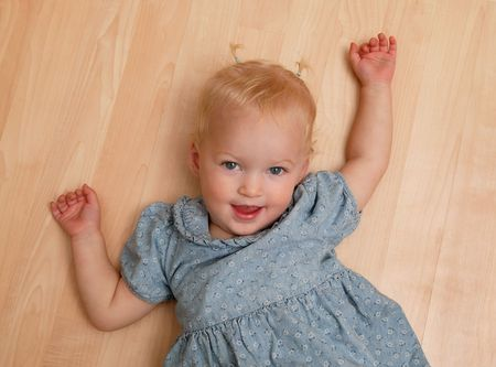 playful behaviour: Playful little girl on hardwood floor, looking up at her daddy