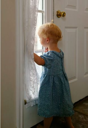 looking out: Toddler waiting by window for parent to return Stock Photo