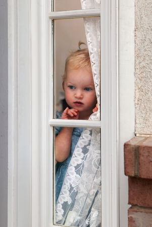 Abandon Child - little girl waiting by window for parent to return photo