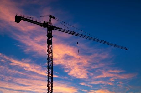 Silhouetted construction crane against a sunrise sky