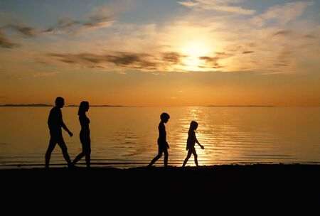 strolling: Family Strolling On Beach At Sunset Stock Photo