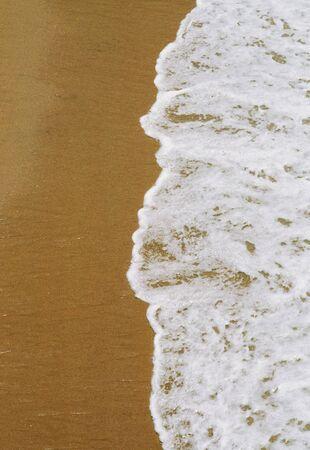 frothy: Lavaggio dolce spumoso onde su una spiaggia di sabbia oceano Archivio Fotografico