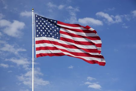 Full American Flag flying in the wind, with blue sky and clouds behind it photo