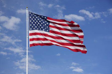Full American Flag vliegt in de wind, met blauwe lucht en de wolken achter Stockfoto