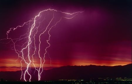 forceful: Real lightning Bolt Strikes - sunrise over city Stock Photo