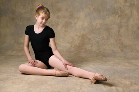 contortion: Teenage girl getting ready for ballet dance with warm-up exercises Stock Photo