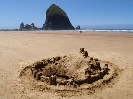 Sand castle on the ocean beach - Cannon Beach, Oregon - Haystack Rock in background