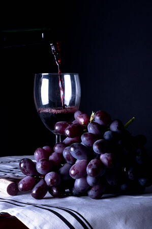 Pouring wine into glass with grapes
