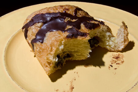 chocolate croissant with two bites on yellow plate