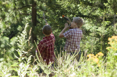 two children playing imaginary games with toy guns and sticks