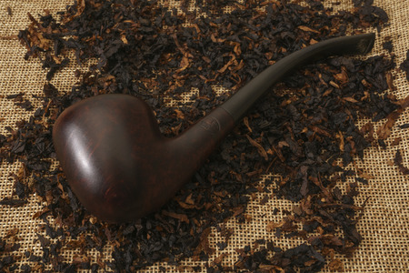 Bent briar pipe with tobacco on burlap Фото со стока