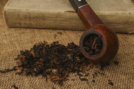 Briar bulldog tobacco pipe on burlap with book