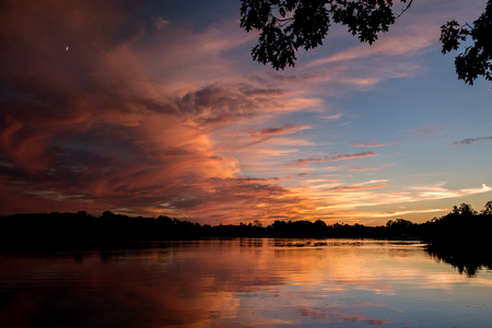 a fiery sunset in Michigan with a reflection over the water