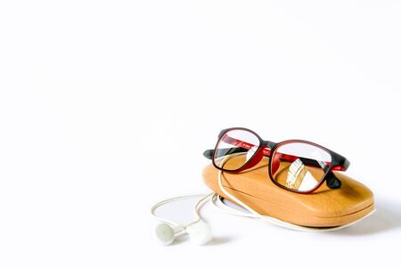 red framed eyeglass placed on its wooden case on white background