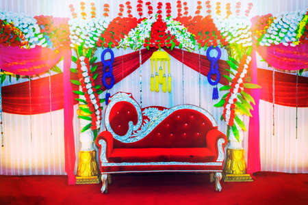 Wedding or wedding reception sitting purpose stage for bride & groom decorated with flowers and royal sofa Stock Photo