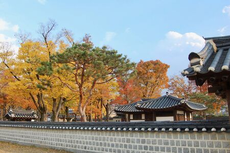 Traditional korean wall and houses in the Jeonju Hanok Village in autumn with colorful trees and blue sky. Korean Traditional vives