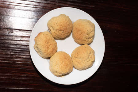 Fives pieces of homemade bread on a white plate, on a wooden table
