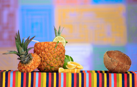 Piña colada with other tropical fruits on a table with mola background