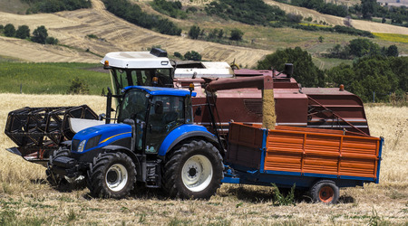 Combine unloading wheat on the trailer of a tractor photo