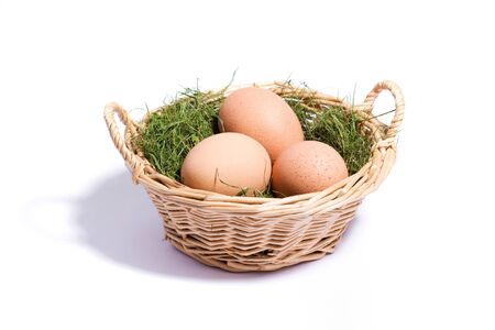 three eggs on the grass in the wicker basket isolated on white close-up photo
